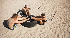 Group of athletes doing crossfit exercise routine on beach. Fitness and healthy lifestyle. Small group of young athletes doing abdominal exercise with a truck stock photography