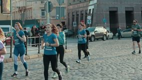 Group of athletes, healthy people running down street, taking part in marathon. LVIV, UKRAINE - OCT 13, 2019: A group of athletes, healthy people running down stock video