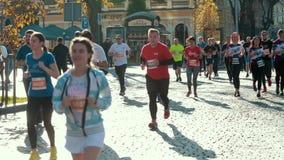 Group of athletes, healthy people running down street, taking part in marathon. LVIV, UKRAINE - OCT 13, 2019: A group of athletes, healthy people running down stock footage