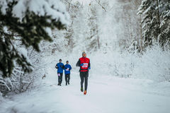 Group athletes runners running in winter snow-covered forest Stock Photography