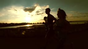 A group of athletes runners - two girls and a man running at city park, near river at sunset, silhouette, slow-motion. Steadicam shot stock footage