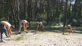 Group of athletes warming up his body and hands before training in the forest. Young strong muscular men stretches stock photos