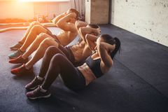 Group of athletic adult men and women performing sit up exercises. To strengthen their core abdominal muscles at fitness training Royalty Free Stock Image