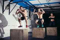 Group of athletic people jumpin over some boxes in a cross-training gym stock image