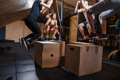 Group of athletic people jumpin over some boxes in a cross-training gym. Group of males and females doing cross fit training at gym stock photos