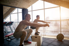 Group of athletic people jumpin over some boxes in a cross-training gym. Two men doing fitness exerciise at gym stock photography