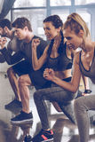 Group of athletic young people in sportswear doing lunge exercise at the gym. Aerobic fitness concept royalty free stock photography