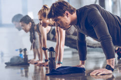 Group of athletic young people in sportswear doing push ups or plank at the gym stock images