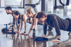 Group of athletic young people in sportswear doing push ups or plank at the gym Royalty Free Stock Photos