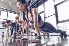 Group of athletic young people in sportswear doing push ups or plank at the gym. Group fitness concept Stock Photography
