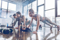 Group of athletic young people in sportswear doing push ups or plank at the gym. Group fitness concept royalty free stock images