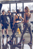 Group of athletic young people in sportswear exercising at the gym Stock Photography