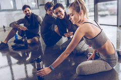 Group of athletic young people in sportswear sitting on floor and resting at the gym Royalty Free Stock Photos