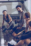 Group of athletic young people in sportswear sitting on floor and resting at the gym Royalty Free Stock Photo