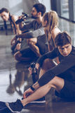 Group of athletic young people in sportswear sitting on floor and resting at the gym royalty free stock image