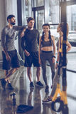 Group of athletic young people in sportswear standing and resting at the gym Royalty Free Stock Photography
