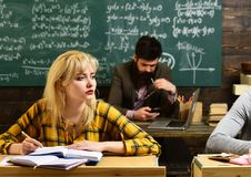 Group of attentive adult students with teacher in classroom at training. Final exam test in university students study. For examination in classroom. Old books stock photos
