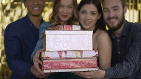 A group of attractive friendly guys make many gifts to the viewer. 4K stock video