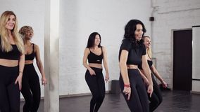 Group of attractive women learning hand moves of bachata dance. Dancing class.