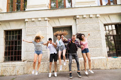 Group of teenage students in front of university jumping high. Stock Photography