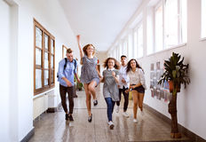 Teenage students in high school hall jumping high. stock photos