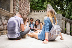 Teenage students at the stone steps in front of university. Group of attractive teenage students sitting on stone steps in front of university, reading and Stock Image