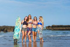 group of attractive women in bikini with surfboard posing in front stock image