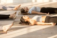 Group of attractive women practicing yoga in Corpse exercise. Group of young attractive people practicing yoga lesson doing Dead Body, Savasana exercise, Corpse royalty free stock photos