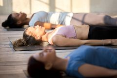 Group of attractive women practicing yoga in Dead Body pose. Group of young people practicing yoga lesson doing Dead Body, Savasana exercise, Corpse pose stock photo