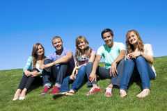 Group of Attractive Young People. Five friends hanging out on a warm summer day outdoors. A multi-ethnic group of young adults Royalty Free Stock Photo