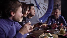 A group of attractive young people in a modern restaurant at a table with snacks and wine. Men and girls drink red wine. And eat snacks. Friends celebrate a stock video