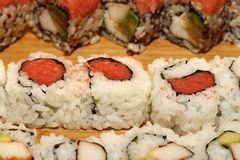 Sushi Fusion Rolls on a platter. A group of avocado, crab sushi appetizers on a wood platter seen at a party Royalty Free Stock Photo