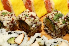 Sushi Fusion Rolls on a platter. A group of avocado, crab sushi appetizers on a wood platter seen at a party Royalty Free Stock Image