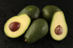 Group of avocado with half on black background Royalty Free Stock Photo
