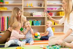 Group of babies in nursery. Nursery teacher and assistant play with kids royalty free stock photography