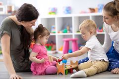 Group of babies playing together with mothers in the classroom in nursery or preschool royalty free stock image