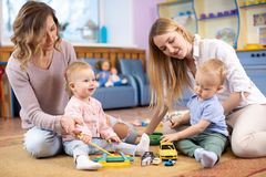 Group of babies toddlers playing with colorful educational toys and mothers in nursery room royalty free stock images