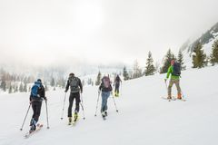 Group of back country skiers walking through a misty valley. Exploring winter fairytale Royalty Free Stock Images