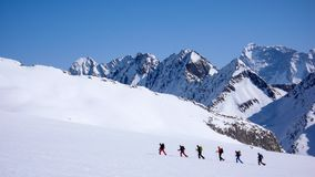 Group of backcountry skiers crossing a glacier on their way to a high summit in the Alps. Near Disentis Stock Images