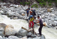 Group of backpacker tourists crossing river stock photo