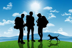 Group of backpackers with a dog on a hill with mountains on back Stock Image