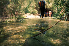 Group of backpackers fording cold river Royalty Free Stock Image