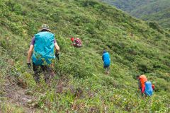 A group of backpackers walking on the mountain. To get to the campground stock photography