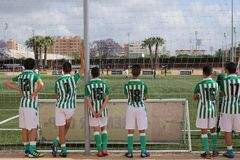 A group of backs of young soccer players are watching a match. A group of backs of young soccer players are watching a football match and are waiting for playing Royalty Free Stock Image