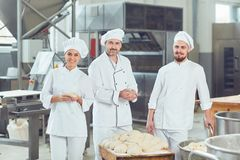A group of bakers smiles at the bakery.  royalty free stock photography