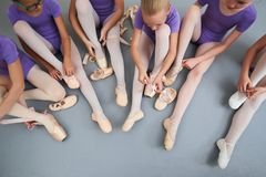 Group of ballerinas put on slippers, top view. Young ballerinas putting on pointe shoes while sitting on the floor. Preparation for dance lesson Stock Image