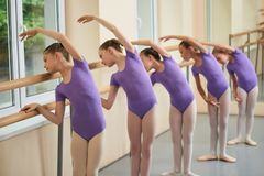 Group of ballerinas training at ballet barre. Young ballet girs in purple leotards practicing at ballet class. Tips for beginning ballet Stock Photo