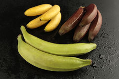 Group of bananas on black background. With water drops Stock Image