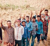 A group of farmers standing around an agricultural field. A group of Bangladeshi farmers standing together and showing victory sign by fingers royalty free stock images