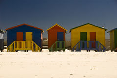 Group of beach huts. Brightly colored beach huts  standing in a long line on a beach Royalty Free Stock Images
